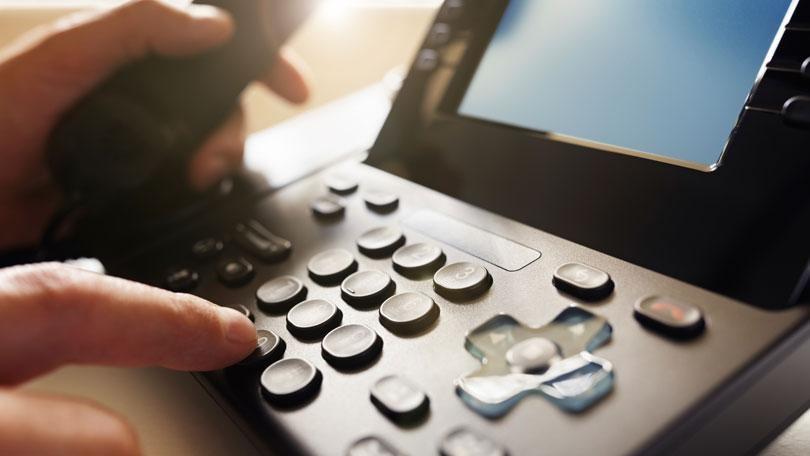 employee-dialing-a-phone